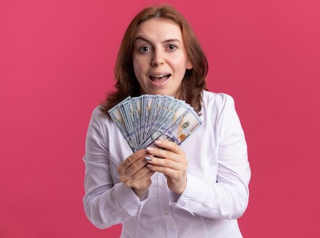 분홍색 벽 위에 서 행복하고 흥분된 전면을보고 현금을 보여주는 흰 셔츠에 젊은 여자