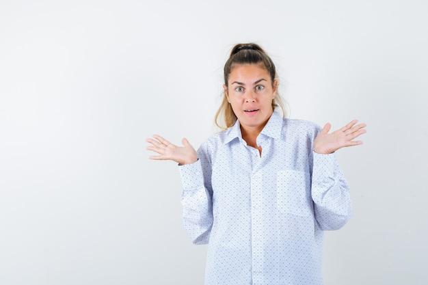 Молодая женщина в белой рубашке показывает беспомощный жест и выглядит озадаченной