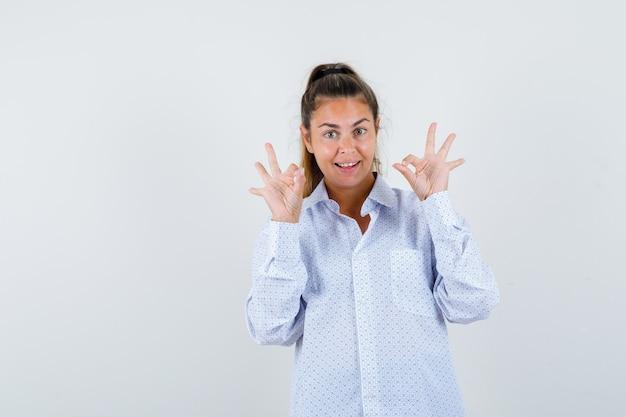 Okの兆候を示し、幸せそうに見える白いシャツの若い女性