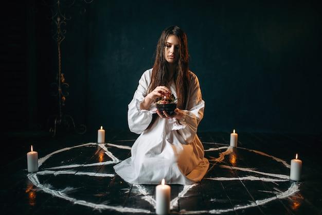 Молодая женщина в белой рубашке сидит в центре круга пентаграммы со свечами и производит ритуал черной магии, черный деревянный пол. оккультизм и экзорцизм