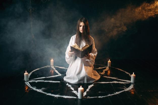 Молодая женщина в белой рубашке сидит в центре круга пентаграммы со свечами и читает заклинание, черный деревянный пол, кругом дым. ритуал темной магии, оккультизм