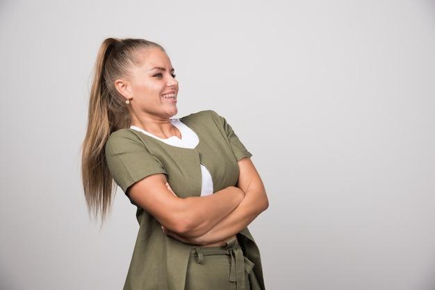 회색 벽에 서있는 흰 셔츠에 젊은 여자.