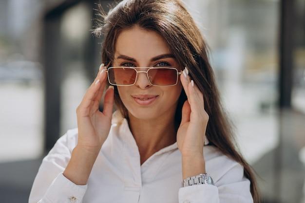 여름 거리 밖을 걷는 흰 셔츠에 젊은 여자