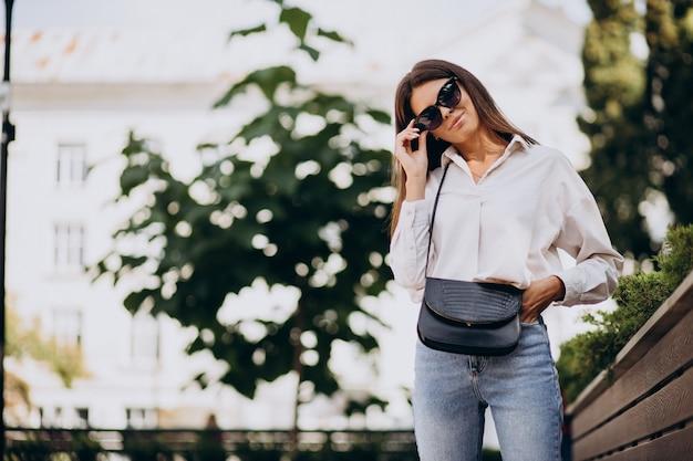 夏の通りの外を歩く白いシャツの若い女性