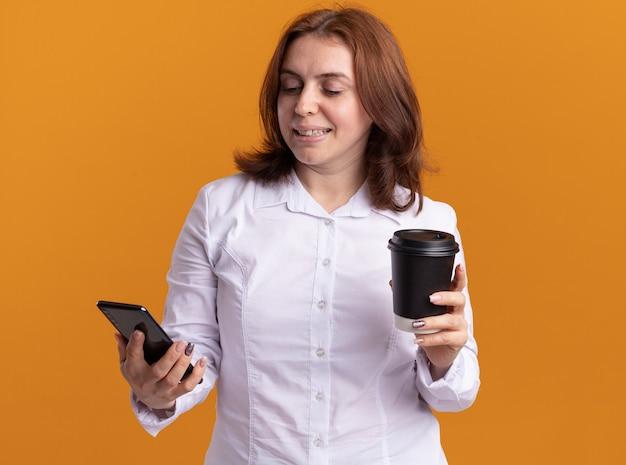オレンジ色の壁の上に立っている顔に笑顔で彼女の携帯電話を見ているコーヒーカップを保持しているスマートフォンと白いシャツの若い女性