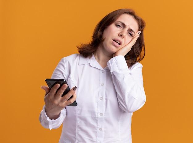 오렌지 벽 위에 서 혼란스럽고 불쾌한 앞을보고 스마트 폰으로 흰 셔츠에 젊은 여자