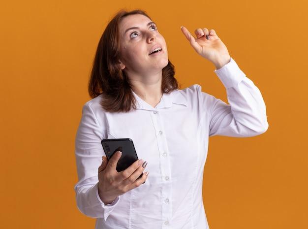 Молодая женщина в белой рубашке со смартфоном, глядя вверх с улыбкой на лице, показывает указательный палец, имеющий новую идею, стоящий над оранжевой стеной