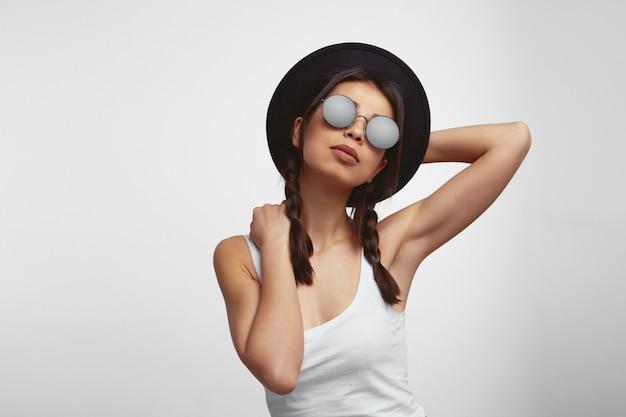 선글라스 모자를 만지고 흰 벽 위에 포즈와 흰 셔츠에 젊은 여자