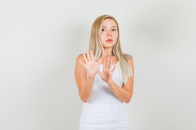 白い一重項の若い女性、停止ジェスチャーを示し、不安そうに見える