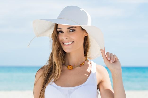 ビーチでリラックスした白い太陽帽子の若い女性