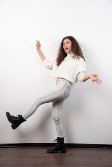白い壁の上に立っている白いセーターの若い女性。高品質の写真