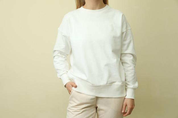Молодая женщина в белом свитшоте против бежевого