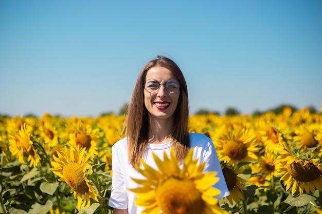 夏の晴れた日にひまわり畑で白いtシャツとメガネの若い女性。