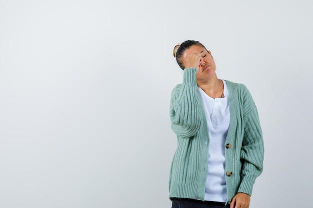 白いtシャツとミントグリーンのカーディガンで額に手を握って、頭痛があり、疲れているように見える若い女性