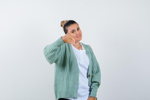 Молодая женщина в белой футболке и мятно-зеленом кардигане приглашает прийти и выглядит счастливой