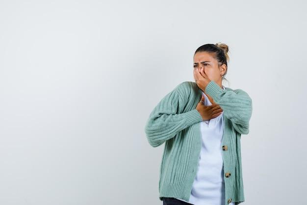 白いtシャツとミントグリーンのカーディガンの若い女性が悪臭のために鼻をつまんでイライラしているように見える