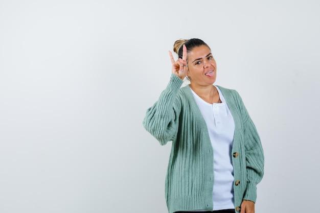 Молодая женщина в белой футболке и мятно-зеленом кардигане показывает рок-н-ролльный жест, высунув язык и выглядит счастливой