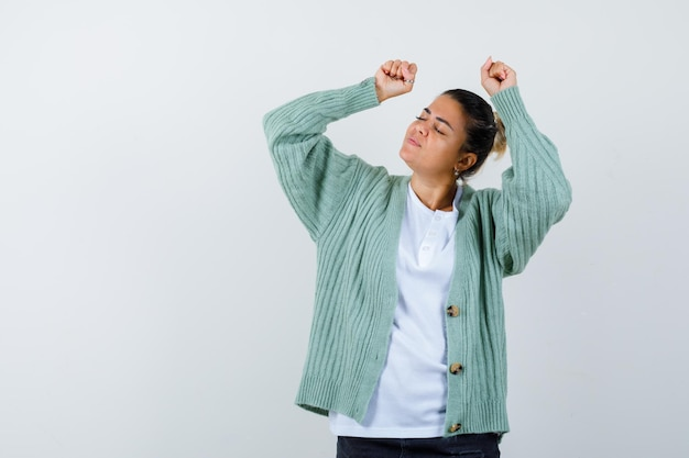 白いtシャツとミントグリーンのカーディガンで勝者のジェスチャーを示して幸せそうに見える若い女性