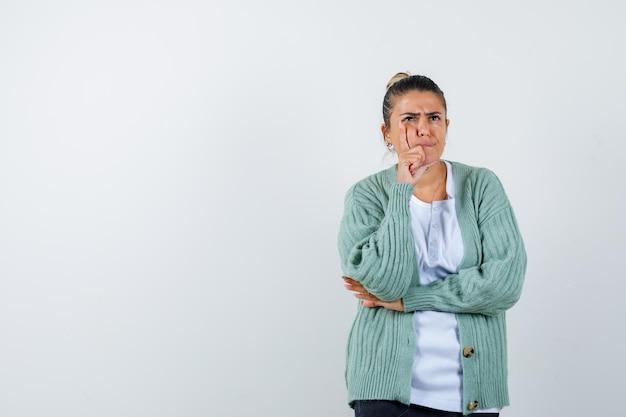 Молодая женщина в белой футболке и мятно-зеленом кардигане стоит в задумчивой позе и выглядит задумчиво