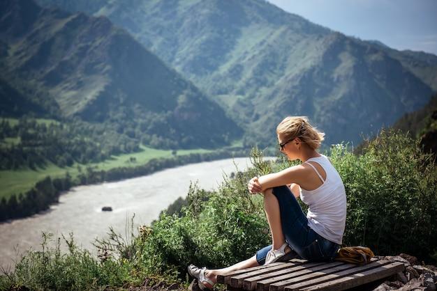 白いtシャツとショートパンツの若い女性は丘の上に座って、日当たりの良い夏の日に山と川の美しい景色を眺めます。
