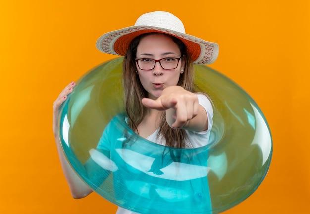 白いtシャツと夏の帽子の若い女性が正面を向いて膨脹可能なリングを保持しています。