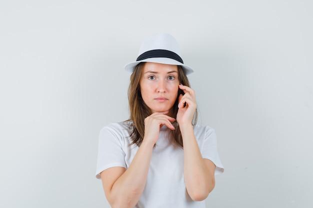 흰색 t- 셔츠, 모자 그녀의 얼굴 피부를 만지고 어지러워 보이는 젊은 여자.