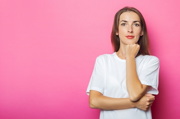 Молодая женщина в белой футболке держит руку под подбородком