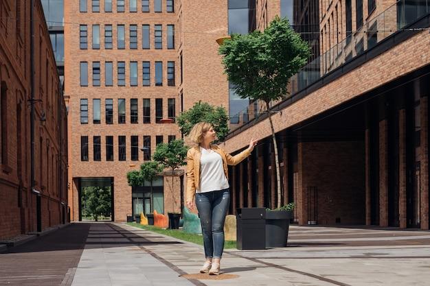 白いtシャツ、ジャケット、ジーンズ、スニーカーの若い女性は、春の日に街の通りを長い散歩する準備ができています。都市景観。観光と喜び。旅行についてのブログ。