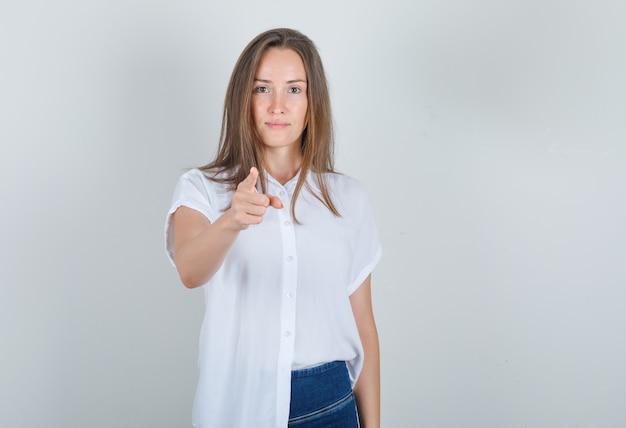 Молодая женщина в белой футболке, джинсах показывает пальцем в камеру и выглядит радостной