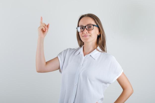 白いtシャツを着た若い女性が指を上向きに元気に見える