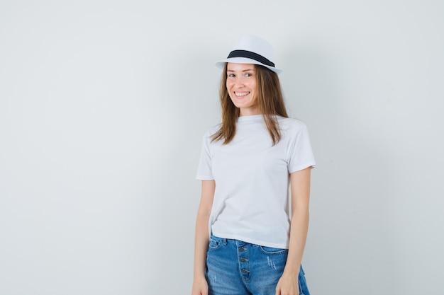 흰색 t- 셔츠, 반바지, 모자와 유쾌한 찾고 젊은 여자.