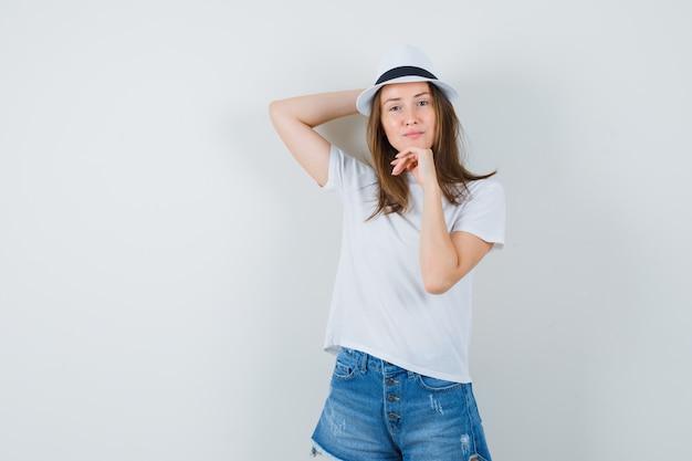 흰색 티셔츠, 반바지, 모자 서 있고 유쾌한 동안 포즈에 젊은 여자.