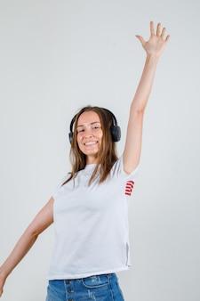 白いtシャツ、腕を伸ばして幸せそうに見えるショートパンツの若い女性