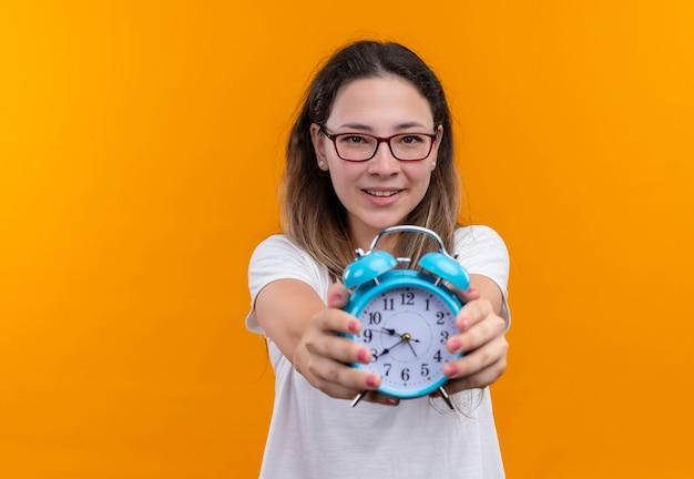 Молодая женщина в белой футболке показывает будильник, весело улыбаясь, стоя над оранжевой стеной