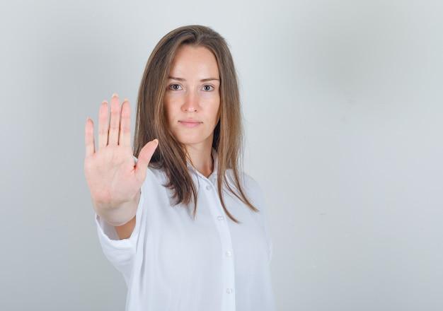 Молодая женщина в белой футболке показывает ладонь камере и выглядит уверенно