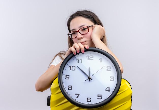 Молодая женщина в белой футболке стоит с чемоданом и держит настенные часы, глядя в сторону с грустным выражением лица над белой стеной