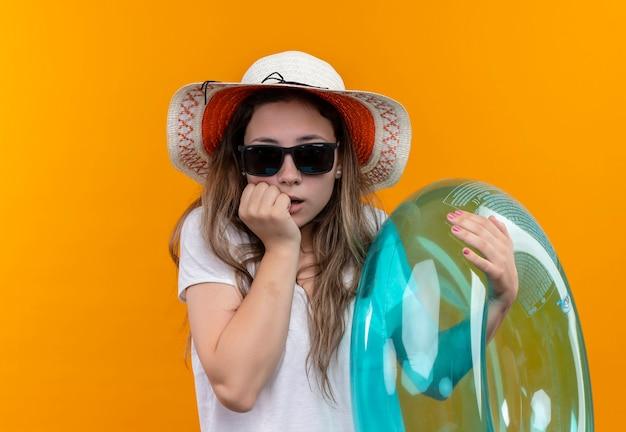 オレンジ色の壁の上に立って驚いて驚いたように見える膨脹可能なリングを保持している夏の帽子をかぶった白いtシャツの若い女性