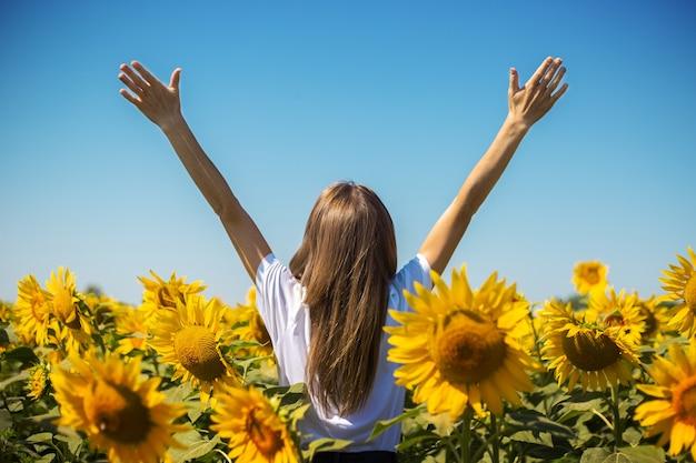 夏の晴れた日にひまわり畑で手を上げた白いtシャツの若い女性。