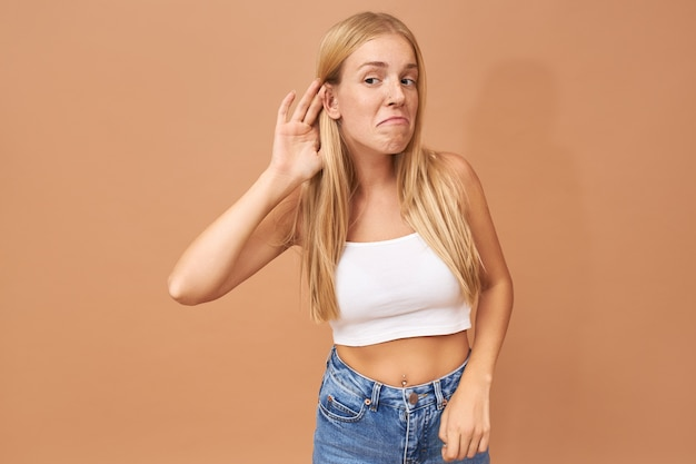 Молодая женщина в белом топе и синих джинсах держит руку у уха, внимательно слушает