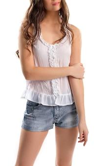 흰색 상단에 젊은 여자. 데님 반바지와 민소매 블라우스. 심플하고 매력적인 의상. 고품질 면직물.