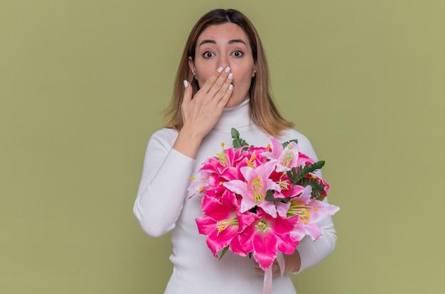 Молодая женщина в белой водолазке держит букет цветов, глядя вперед, изумленно прикрывая рот рукой, празднуя международный женский день, стоя над зеленой стеной