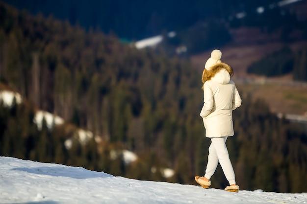 하얀 겨울 옷을 입고 야외에서 걷는 젊은 여성