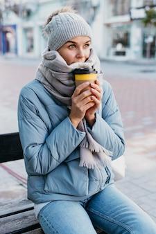 Молодая женщина в зимней одежде держит чашку кофе