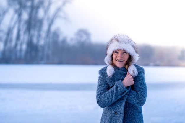 自然の中で冬の服を着た若い女性