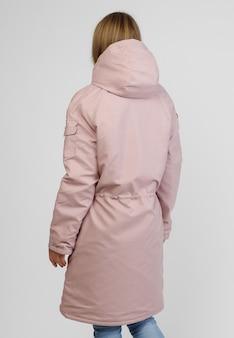 白い背景の上の冬の服を着た若い女性。ダウンジャケットを宣伝するための写真のコンセプト