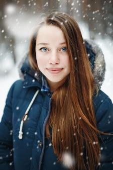 雪の下に立って、笑顔で、カメラを見て冬服の若い女性。冬の森の風景と背景の降雪。