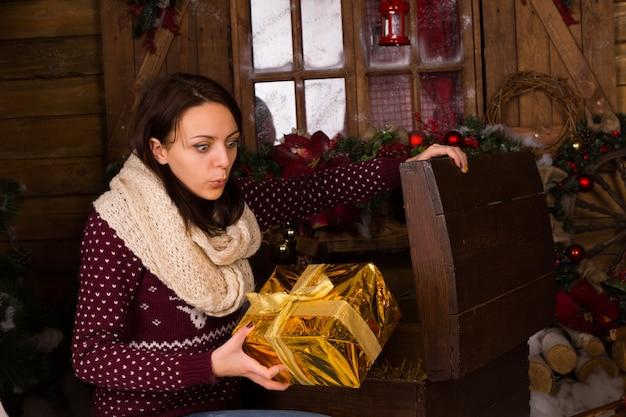 Молодая женщина в зимнем наряде с удивленным выражением лица держит золотой рождественский подарок из деревянного сундука