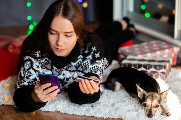 겨울 스웨터를 입은 젊은 여성이 집에서 전화를 통해 작은 강아지와 함께 크리스마스 구매를 온라인으로 만듭니다.