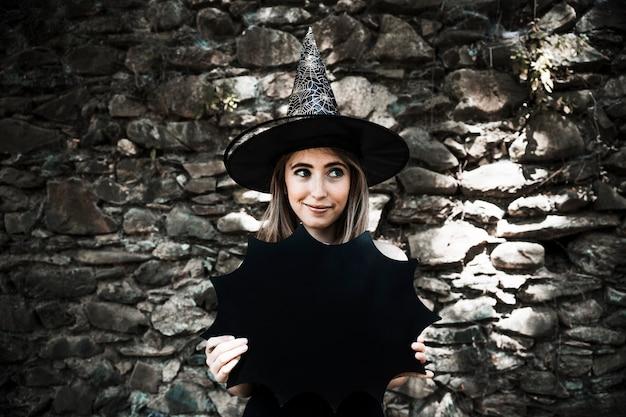 할로윈 장식 들고 멀리보고 마녀 모자에있는 젊은 여자