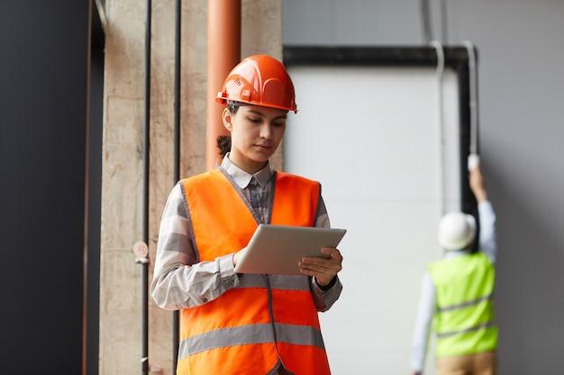 건설 현장에서 작업하는 동안 작업 헬멧과 디지털 태블릿을 사용하는 반사 조끼에 젊은 여자